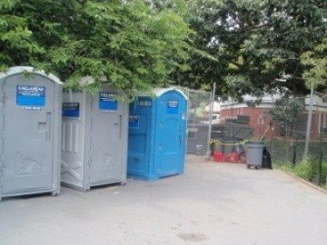 Washington Square Park temporary rest rooms old buildings behind them